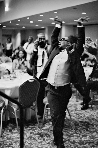 A person in a suit and shades has hands and arms raised as they vogue