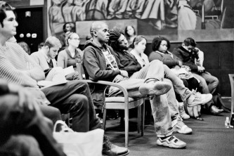 A seated audience listen intently to a panel discussion