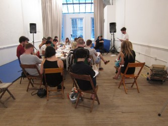 People sit at a long table in a white room as folks listen to a standing figure