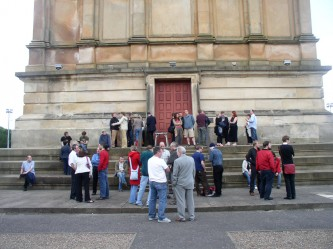 An audience assembled outside Hamilton Mausoleum, a large stone edifice