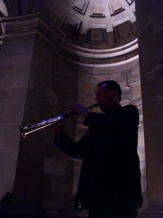 John Butcher playing a soprano saxophone in a domed alcove