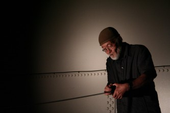Akio Suzuki holding a spring in an old tank, rivets on the wall behind