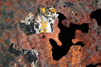 Rusted metal and peeling paint with a dark recess