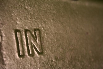 Close up of a metallic surface with the word 'IN' in relief