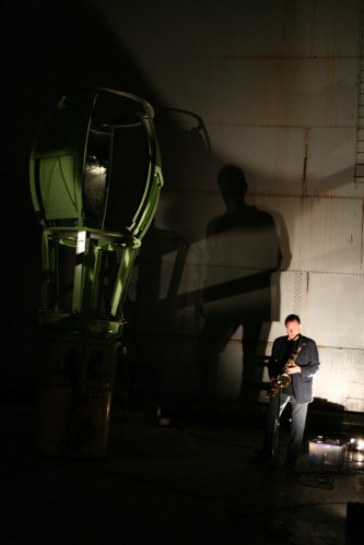 John Butcher playing tenor sax in an oil tank next to old metal machinery