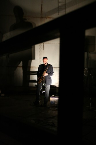 John Butcher holding a tenor saxophone in darkness in an oil tank