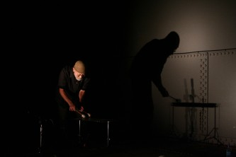 Akio Suzuki playing a percussion instrument inside an oil tank