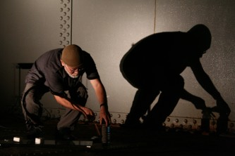 Akio Suzuki and shadow moving things around on the floor of an oil tank