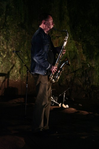 John Butcher playing a tenor saxophone in smoo cave