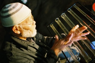 Akio Suzuki touching glass rods in a cave