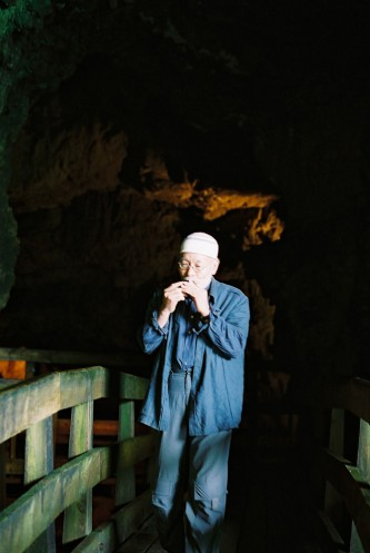 Akio Suzuki blowing a small object on a bridge in a cave