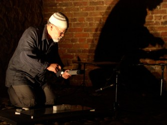 Akio Suzuki playing a percussion instrument inside Tugnet Ice House