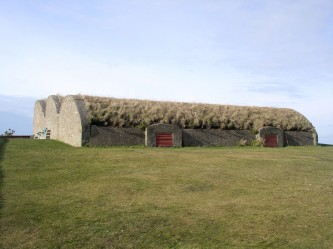 Grassy roofs of Tugnet Ice House, surrounded by grass and low walls