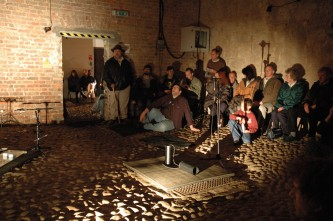 An audience assembled inside Tugnet Ice House, cobbled floor