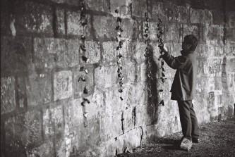 Ikuru Takehashi hanging strings of small objects on a wall