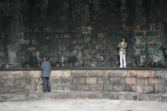 Tamio and Ikuru looking around at a stone walled space with green patches