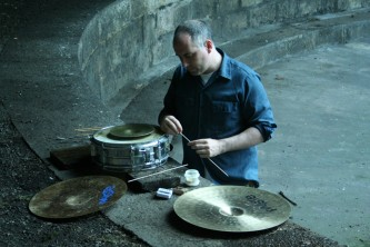 Sean Meehan selecting a stick from several sticks near some cymbals