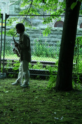 Tamio Shiraishi playing saxophone under a tree in white jeans and coat
