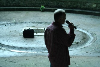 Denis Wood talking into a microphone in a little circular space