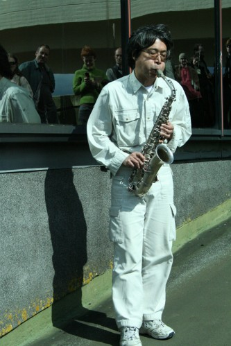 Tamio Shiraishi dressed in white plays saxophone on a walkway in Cumbernauld
