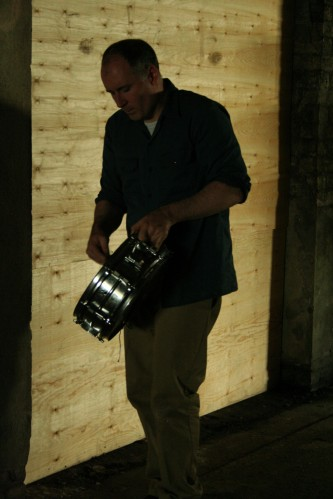 Sean Meehan carrying a snare drum through an underpass lined with plywood