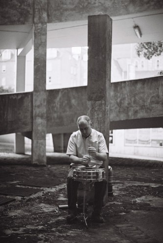 Sean Meehan playing a cymbal with a dowel rod surrounded by concrete forms