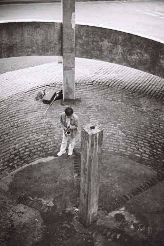 Tamio Shiraishi playing saxophone in a concrete spiral: white jeans white shoes