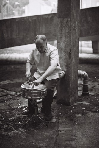 Sean Meehan playing a snare near concrete forms in Dundee