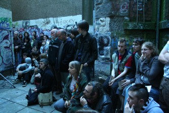 An audience assembled in a back street of Dundee