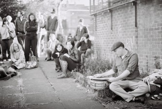 Sean Meehan sitting on the ground with snare and cymbals