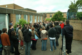 An audience assembled around Denis Wood speaking in Easterhouse
