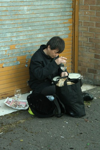 Ikuru Takehashi playing a snare with a wine glass and water near a metal door