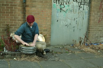 Sean Meehan holding a cymbal against a snare near a metal door, red hat
