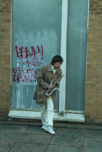 Tamio with saxophone and graffito in Easterhouse