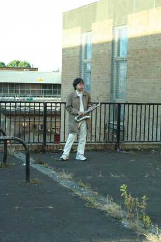 Tamio standing alone near a fence holding a saxophone