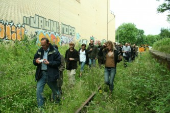 An audience walking along an abandoned railway line: graffiti and plants