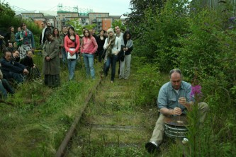 An audience watching Sean Meehan play a cymbal on a railway track in Edinburgh