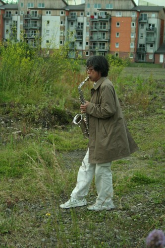 Tamio Shiraishi playing saxophone in a grassy place in Edinburgh
