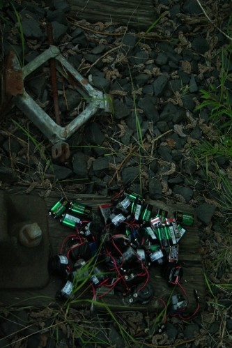 A bundle of batteries and electronic devices in a heap near track ballast
