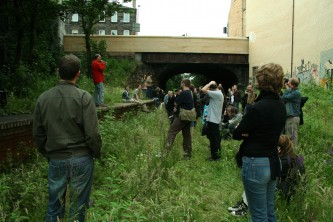 Denis Wood talking to an audience from an old railway platform