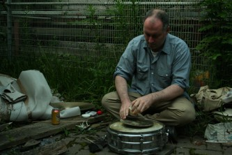 Sean Meehan playing a cymbal on a snare next to a fence