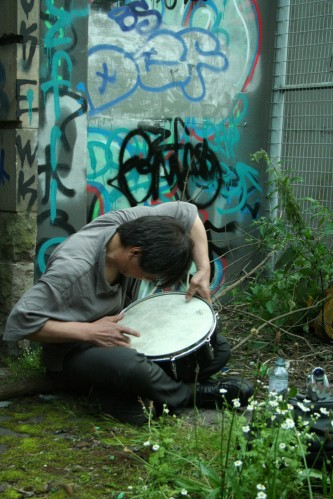 Ikuru Tahehashi playing a snare next to a graffiti covered wall and a fence