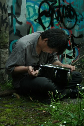 Ikuru Takehashi playing a snare on the ground against a wall