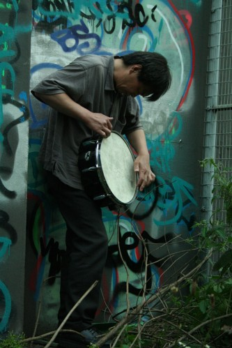 Ikuru Takehashi playing a snare standing against a graffiti covered wall