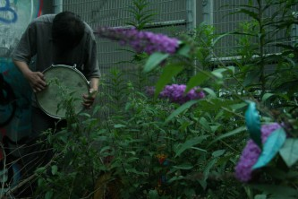 Ikuru Takehashi playing a snare drum among buddleia and nettles