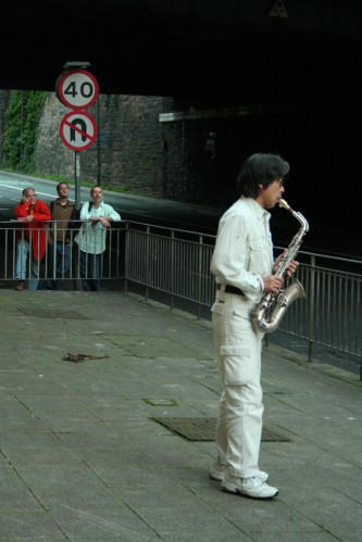 Tamio Shiraishi playing saxophone next to a road: 40 mph speed limit sign