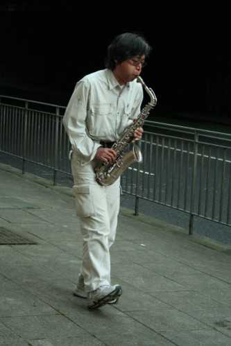 Tamio Shiraishi playing saxophone next to a fence in Edinburgh