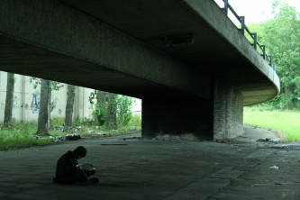 Ikuro Takehashi sitting under a motorway flyover playing a snare
