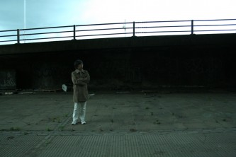 Tamio with folded arms stands by a motorway in a raincoat