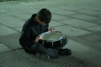 Ikuro Takehashi sitting on ribbed concrete tiles playing a snare
